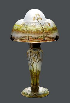 DAUM NANCY TABLE LAMP, c. 1900 Light blue glass, etched and enamelled. Mushroom-shaped, decorated with an autumn landscape. The foot signed Daum Nancy. H 35 cm.