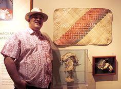 Nani I Ka Hala: Weaving Hawai'i exhibit preview. Micheale Naho'opi'i standing next to a beautiful mat he wove.