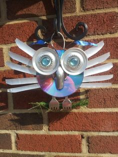 Owl cd. All reusable stuff. Wings and eyes are made out of soda cans.nose is a old spoon. O dont hot glue.. It will fall apart in the cold weather. I used JB weld.