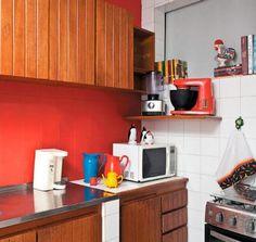 Jarras e açucareiros velhinhos conquistaram visual pop na cozinha após um banho de cor. Os azulejos brancos receberam uma camada de tinta vermelha, que contrastou com os armários de madeira e com a geladeira de inox. Projeto de Valentina Rocha.