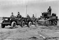 """M3A1 Stuart tank being towed by 2 G503 jeeps. Circa 1943, location unknown. The Stuart in the picture has a welded hull which replaced the original riveted armor on pre-1942 Stuarts. Note the """"barrel"""" shaped tanks on each sponson. These 25 gallon tanks were encased in a bullet-sealing covering and carried extra gas (or diesel) effectively doubling the Stuart's range to 140-180 miles."""