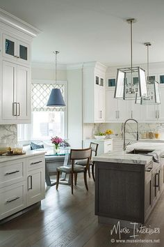 Gorgeous kitchen features glass and nickel lantern illuminating a gray wash center island topped with statuary marble fitted with a stainless steel sink and pull out faucet.