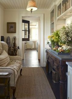 Charming, country style hallways with dark wood and white paint. I love the built-ins and the vintage chest/drawer.