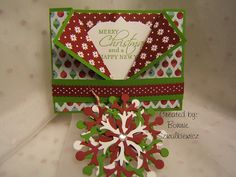 """fancy gate fold covered with decorative scrap book papers.  In the inside of the """"V"""" fold is a snowflake ornament that has been tucked in place.  The strip seen in front is actually a belly band that holds it all together.  From the mother-daughter team at the CraftiBlog http://craftiblog.wordpress.com/2012/12/13/2012-12-13-december-stamp-camp-card-3/"""