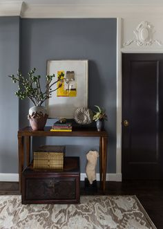 White walls in the entryway were painted a blue grey to create immediate drama. The doors, also originally white, were painted with Benjamin Moore's Graphic paint to complement the dark floors.  The console table is from Hickory Chair and the Khotan rug is from Stark.  The trunk is an Asian antique and the art is by Dolby Chadwick.