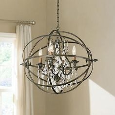 This chandelier features hand-worked wrought iron enclosing crystal pendants and candle lights.