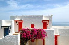 Imagem 10/22: Casas gregas tradicionais, com paredes caiadas, telhado ausente e esquadrias em cores vivas.