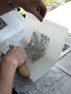 Angie Lewin hand burnishes her 'Alphabet and Feathers' wood engraving for the V&A Museum in London.