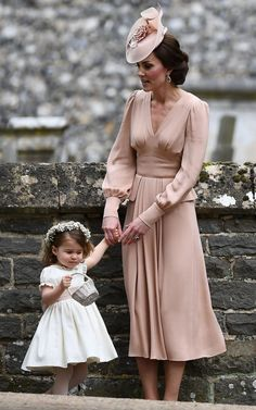 The Duchess of Cambridge stands with her daughter Britain's princess Charlotte, a bridesmaid - Credit: JUSTIN TALLIS/AFP/Getty Images
