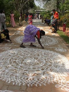 """""""Kolam Fest"""" - photo by Manohar_Auroville, via Flickr;  """"The kolam, or 'rangoli' is a traditional mandala ... that women design in front of their houses during festivities."""" Each year, """"hundreds of women gather from Auroville and the nearby villages to show their skills in this particular art"""" at this festival in Bharat Nivas, a pavilion in Auroville's International zone, in Puducherry, India."""