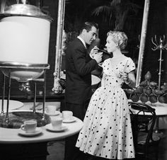 1954, New York, New York, USA --- Movie star Tippi Hedren models a polka dot dress by Jacques Fath in the Plaza Hotel lobby. A male model in a suit smokes next to her.