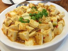 Ma Po Tofu - a medium firm tofu stir fried with ground pork in a spicy chili sauce. Topped with green onions. Chinese comfort food. Excellent with steamed rice.