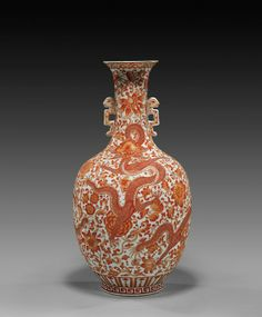 DAOGUANG-STYLE PORCELAIN DRAGON VASE. Finely detailed, Chinese coral red decorated porcelain dragon vase; of ovoid form with slim neck and flared mouth, with design of five-clawed writhing dragons amid a floral ground, with two chilong flange handles; Daoguang seal mark, but probably early Republic Period; H: 12 3/4""