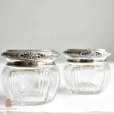 Antique Sterling Silver and Etched Cut Crystal Vanity Jars, this exquisite pair of dresser jars has fine luxury quality lids with an H monogram on the top. The lids are beautifully made, showing off the exceptional mastery of the maker, with striped Art Nouveau design, laurel leaf garland vine and floral embellishments. Marked by the maker and for STERLING. The jars have a delicate and romantic etched rose on each of the six panels. Divine treasure for your French vanity table, or guest…