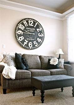 Black and white room makeover. I love the over-sized clock above the couch! What a great piece of art!
