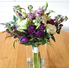 Purple and white bouquet filled with purple stock, creamy white lisianthus, lavender spray roses