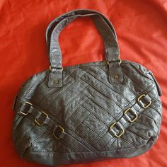 A gray leather style handbag It's a larger shoulder bag that holds a lot with only one zipper pocket on the inside. There's no damage to the bag and it's slate gray in color and dark purple fabric on the inside. Bags Shoulder Bags