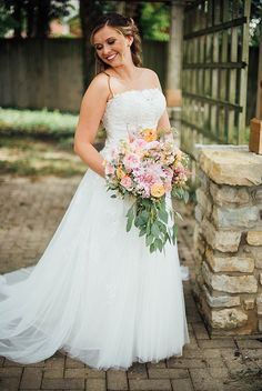 we love the bride's pastel pink and peach wedding bouquet with cascading greens