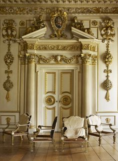Jamb Limited - Brand - London - Neoclassical - Great Room - Foyer - Entryway - Vignette - White - Gold - Luxe - Ornate - Wood Floor - Upholstered Chair - Velvet - Double Door - Columns