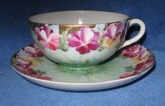 Antique eggshell porcelain teacup and saucer with hand-painted Pansies
