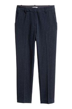 Een broek van elastische, geweven kwaliteit met een normale taille en smal toelopende pijpen. De broek heeft steekzakken en een gulp met een blinde haak-en-