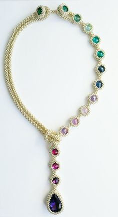 This striking necklace is made with silver colored Miyuki seed beads,(colorfast!) , various colors rivolis and a purple glass drop pendant. The clasp is made with matching rivolis, easy on, easy off. The necklace is very classy and elegant, perfect for a special occassion. The length of the necklace is 32 cm / 12.6, The purple pendant measures 3.3 cm x 2.3 cm You will receive the necklace with an organza gift bag, and will be shipped with registered mail. www.wirwarkralen.nl has mad...