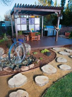 After: In the newly redesigned backyard, cut-log steps lead to a floating deck with shade structure. This wild and different metal water feature, adds visual and auditory interest.