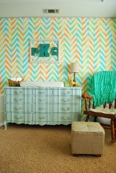 DIY Ikat + Chevron Accent Wall in the Nursery - painted the wall different colors then stenciled white chevron to create the ikat look.