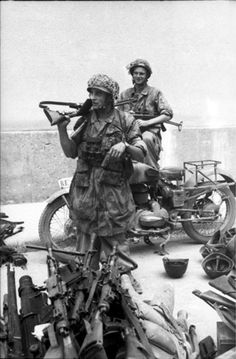 German paratrooper with Italian-made automatic rifle. In the foreground there are more weapons most likely seized from Italian soldiers; the picture was most likely taken after September 8, 1943, when the Germans began to disarm their former Italian allies.