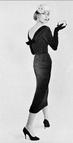 1955 Ghislaine Arsac is wearing a tight draped jersey sheath edged in velvet along the neckline ending in bow in deep v in back by Jacques Fath, photo by Guy Arsac