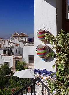 Mediterranean mood: colourful pots, ornamental tiles, white houses and the deep blue sky. Frigiliana, Andalusia, Spain. Postcard from Costa del Sol.