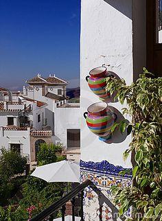 Mediterranean mood: colourful pots, ornamental tiles, white houses and the deep blue sky. Frigiliana, Andalusia, Spain.