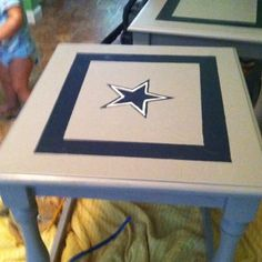 Old living room end table. Sanded down with electric sander. Painted with left over NFL paint from room. Hand painted star using overhead projector.