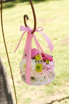 Pretty idea for tea party decoration. Shepherds hook garden stake with ribbon, tea cup and saucer, and flowers. Beautiful