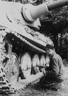 A King Tiger getting some camo paint applied in field conditions