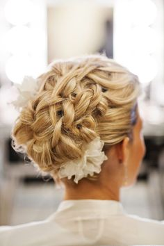 Pretty wedding updo with a flower accent.