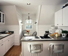 Disappearing Acts  In open-plan kitchens, installing white appliances with white cabinets keeps your range, dishwasher, and refrigerator from standing out. Avoid visually harsh dark holes without the cost of trim panels. Use white to camouflage a mix of textures like this quirky top-floor kitchen.