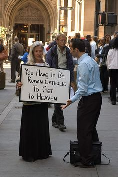Roman Catholic  This may very well be one of my best shots ever. It is taken on Wall Street, right in front of Trinity church, and the person to the right is arguing with this woman, probably about what it takes or doesn't take to get to heaven...