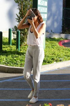 Selena Gomez wearing Stuart Weitzman Nuggets Croco Embossed Leather Sneakers in Ice, Puma Yogini Lux Sports Bra, Are You I Am Kasia Tank in White and Puma Prime Sweatpants