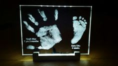 Lit-up hand and foot print in glass plate with light base
