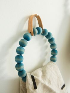 DIY Towel Ring with wood beads and a leather hanger.