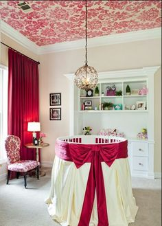 Deep pink nursery with wallpapered ceiling. Very feminine.