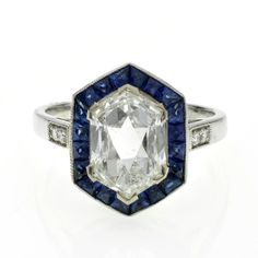 A diamond and sapphire cluster ring, surrounded by calibre cut rub over set sapphires in the stlye of a hexagonal target ring, with diamond set shoulders mounted in platinum.