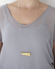 funny shape brass pendant on silver chain.