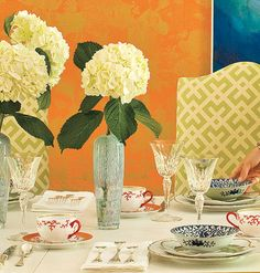 Mixing colors and patterns is key in this dining room, and the table setting is no different.