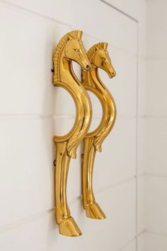 Gold-colored brass cabinet pulls, in the shape of twin horses.