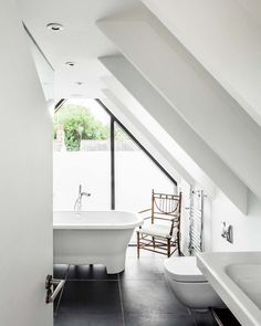 House in Oxford by Waind Gohil Architects  black tiles, tub, cute chair and plenty of sunlight
