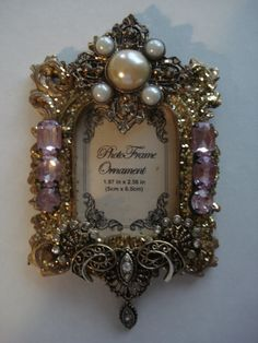 Cute lil ornament frame....but this actually inspired me to maybe make light switch plates covered in pearls and jewels like this!
