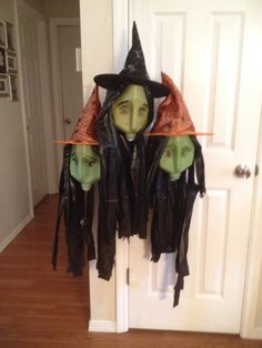 Three sister witches - gallon milk jug, black trash bag, dollar store hat, wire, a washer, green craft paint, a sharpie & a glue gun.