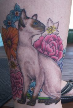 Cartoon style colored leg tattoo of cute cat with flowers